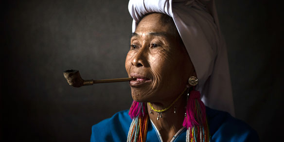 Woman from Karen hill tribe smoking tobacco pipe, Northern Thailand