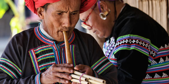 Karen man in traditional costumes playing a flute, Northern Thailand