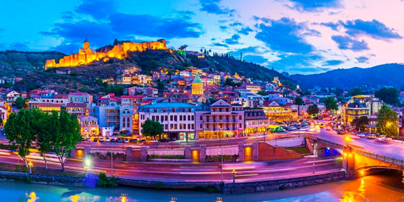 Panorama of the old town, located on Sololaki hill, crowned with brightly illuminated Narikala fortress, on Kura river, Tbilisi, Georgia