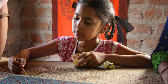 A gujarati girl in the process of textile handpainting, Gujarat, India