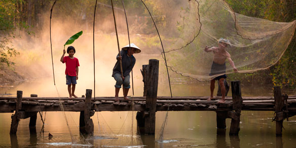 Thai family on wooden bridge helping each other to catch fish, Thailand