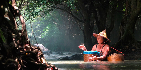 A Thai woman fishing in a river, Thailand